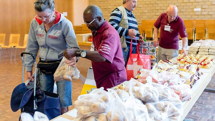 """Freiwillige helfen in einer der 120 Ausgabestellen von """"Tischlein deck dich"""" Kunden beim Auswählen und Einpacken der Lebensmittel. Pro Einkaufskorb bezahlen die Kunden einen Franken."""