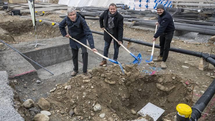 Roland Verardo, Präsident der Baugenossenschaft Schönheim, Gemeindepräsident André Bender und Philipp Oesch von Haerle Hubacher Architekten vergraben die Zeitkapsel.