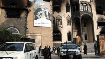 UNO-Fahrzeuge vor einem beschädigten Haus in Sanaa