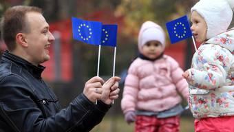 Ukrainisches Kind und sein Vater halten EU-Fähnchen (Archiv)
