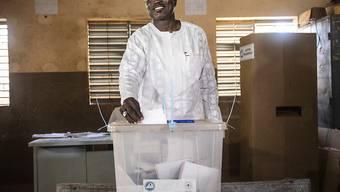 Eddie KomboÔgo, Kandidat der Opposition- Kongresses f ̧r Demokratie und Fortschritt (CDP), wirft seinen Stimmzettel f ̧r die Pr‰sidentschafts- und Parlamentswahlen in eine Wahlurne. Foto: Sophie Garcia/AP/dpa