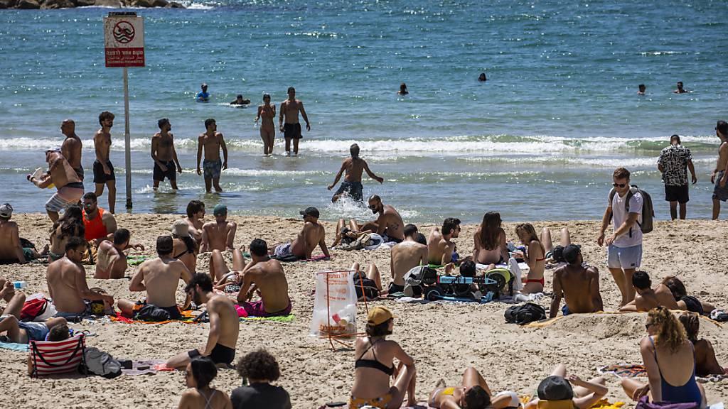 Menschen verbringen den Tag in der Sonne am Strand in Tel Aviv. Durch die fortgeschrittene Impfkampagne in Israel werden die Corona-Maßnahmen immer weiter aufgehoben. Foto: Ilia Yefimovich/dpa