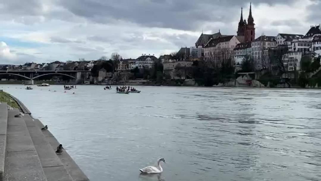Eine Gugge treibt am Dienstag tonlos mit schwarzen Ballons den Rhein hinunter.