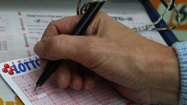 Eine Lottospielerin füllt ihren Lottoschein aus (Symbolbild).