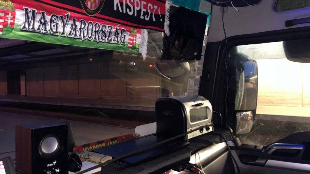 Chauffeur platziert Mikrowelle auf der Ablagefläche des Armaturenbrettes.