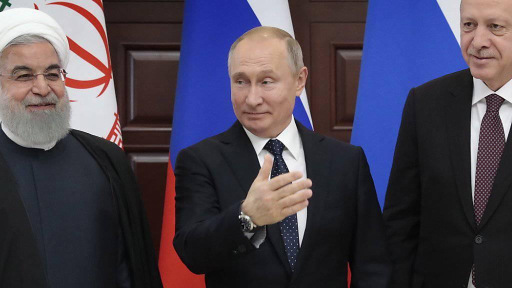 Russlands Präsident Wladimir Putin (Mitte) fordert am Syrien-Gipfel in Sotschi die USA auf, die Truppen rasch aus Syrien abzuziehen. Am Gipfel vereinbarte er mit dem türkischen  Staatschef Recep Tayyip Erdogan (rechts) und Irans Präsident Hassan Ruhani, das Vorgehen im Syrien zu koordinieren.