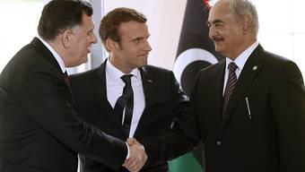 Der französische Präsident Emmanuel Macron (Mitte) begrüsst den Chef der libyschen Übergangsregierung Fajis al-Sarradsch (links) und den im Osten Libyens mächtigen General Chalifa Haftar (rechts) zu den Verhandlungen bei Paris.