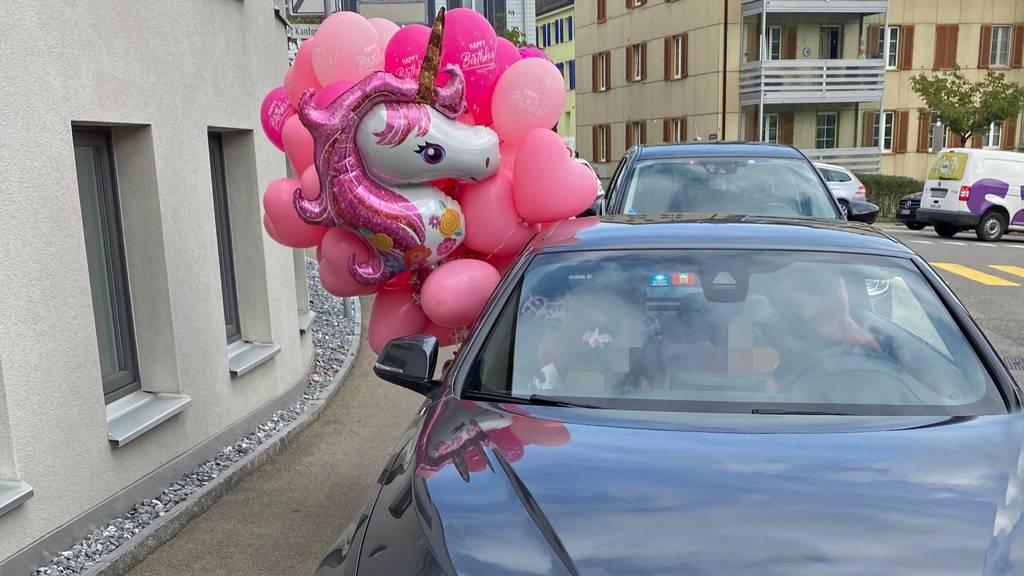 Ballone aus Autofenster gehalten und Kind auf Schoss – Anzeige und Busse