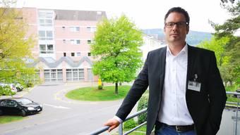 Spitaldirektor Daniel Schibler auf dem Balkon seines Büros. Im Hintergrund das Spital Menziken.