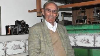 Traugott Berner sitzt auf dem Kachelofen im Dorfmuseum. Den Bauern «läschelte» er viele Geräte und Museumsstücke ab.