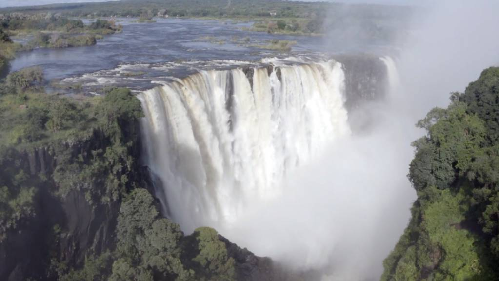 Die angeblich ausgetrockneten Victoria-Wasserfälle werden nun von Wasser überströmt, doch der Tourismus bleibt wegen der Pandemie aus. Foto: Columbus S. Mavhunga/dpa - ACHTUNG: Nur zur redaktionellen Verwendung im Zusammenhang mit der aktuellen Berichterstattung und nur mit vollständiger Nennung des vorstehenden Credits