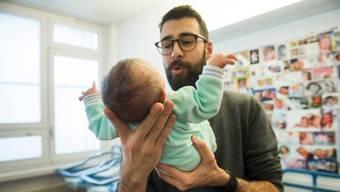 Ein Vater mit neugeborenem Kind im Spital von Bellinzona.