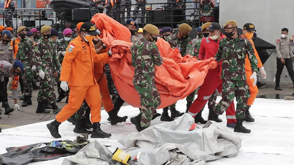 Indonesische Rettungskräfte bergen Leichenteile und Trümmer nach dem Absturz eines Passagierflugzeuges.