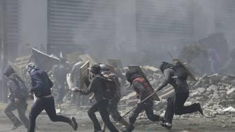 Protestierende Regierungsgegner flüchten am Samstag in Quito vor dem Tränengas der Polizei.