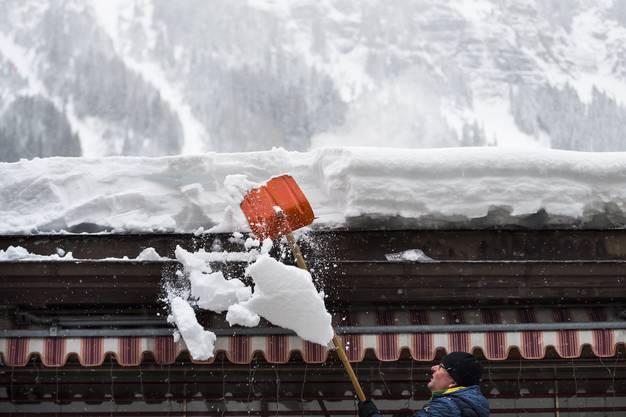 Ein Mann befreit ein Hausdach in Wengen im Berner Oberland von den Schneemassen.