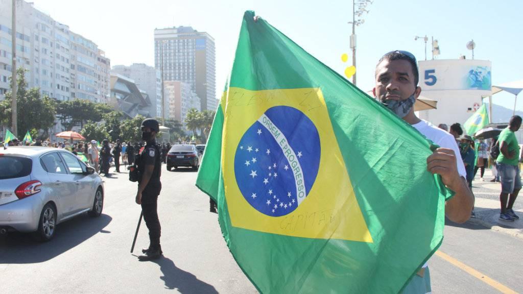 Ein Unterstützer des brasilianischen Präsidenten Bolsonaro hält bei einem Protest an der Copacabana eine brasilianische Fahne hoch. Foto: Fausto Maia/TheNEWS2 via ZUMA Wire/dpa
