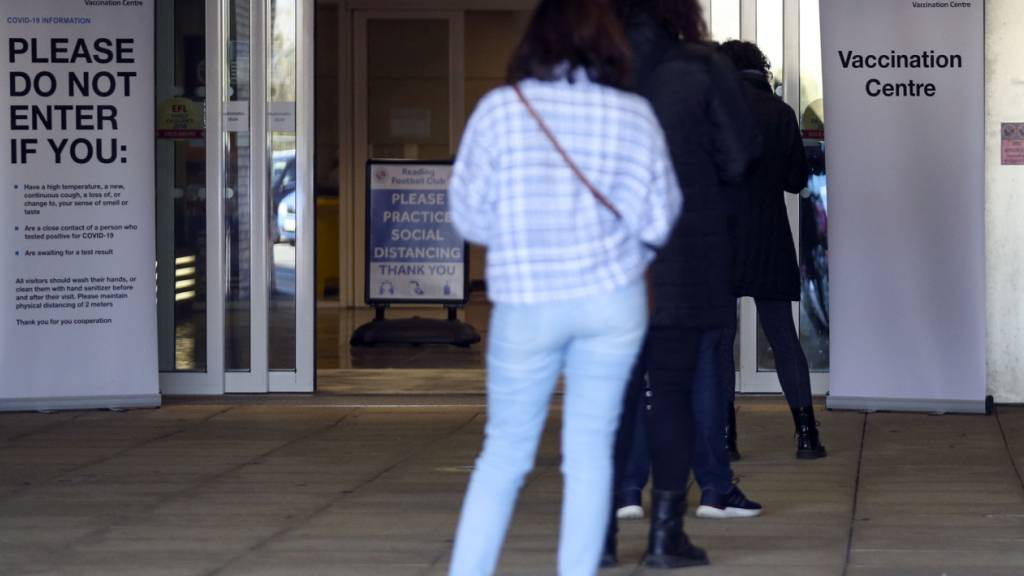 Menschen stehen vor einem Impfzentrum in Reading in Großbritannien. Foto: Steve Parsons/PA Wire/dpa
