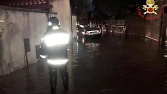 HANDOUT - Ein Feuerwehrmann steht in einer überfluteten Straße auf Sardinien. Auf der italienischen Mittelmeerinsel hat ein Unwetter schwere Schäden angerichtet. Foto: Vigili del Fuoco/dpa - ACHTUNG: Nur zur redaktionellen Verwendung im Zusammenhang mit der aktuellen Berichterstattung und nur mit vollständiger Nennung des vorstehenden Credits
