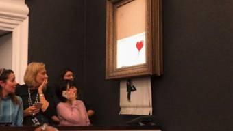 Verdutzte Zuschauer bei der Sotheby's Auktion: Soeben wurde Banksys Bild geschreddert.