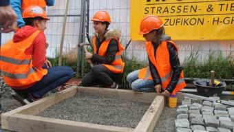 Schülerinnen der 3. Bezirksschule Wohlen machen unter Anleitung erste Versuche im Strassenbau und gehen die Sache behutsam an.