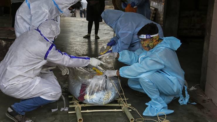 Angehörige eines Mannes, der an den Folgen einer Corona-Erkrankung gestorben ist, bereiten die Einäscherung seiner Leiche auf dem Vadaj-Friedhof vor. Indien ist weltweit momentan das am zweitstärksten vom Coronavirus betroffene Land. Foto: Ajit Solanki/AP/dpa