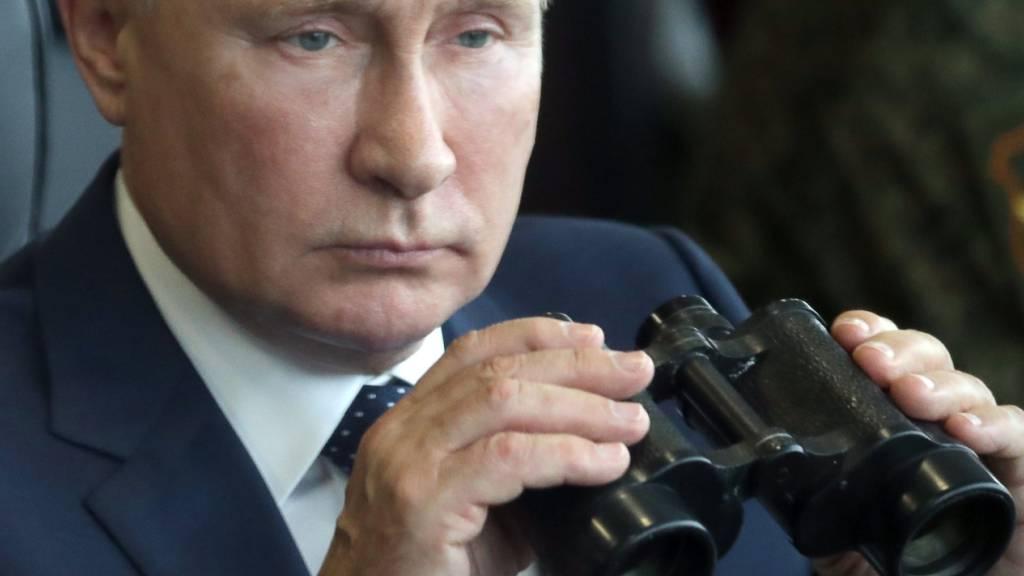 Russlands Präsident Wladimir Putin hält während seines Besuchs bei der gemeinsamen strategischen Übung der Streitkräfte von Russland und Belarus auf dem Truppenübungsplatz Mulino in der Region Nischni Nowgorod ein Fernglas in den Händen. Foto: Sergei Savostyanov/Pool Sputnik Kremlin/AP/dpa