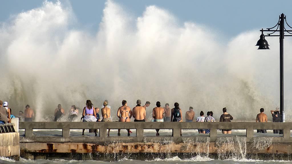 Strandbesucher stehen vor einer großen Welle, die wegen des starken Tropensturms «Laura» zustande kommt. Ungefähr 100 Anwohner kamen zum beliebten Pier, um sich den Wind und die großen Wellen anzusehen. Foto: Rob O'neal/The Key West Citizen/dpa