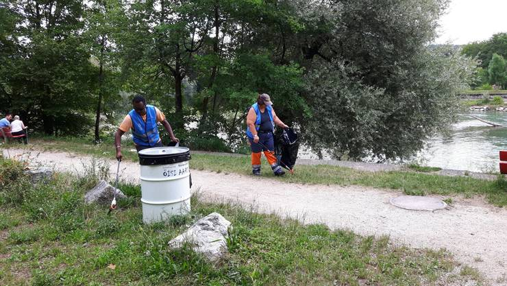 Zwei Oltech-Mitarbeiter räumen Abfall am Aareufer weg.