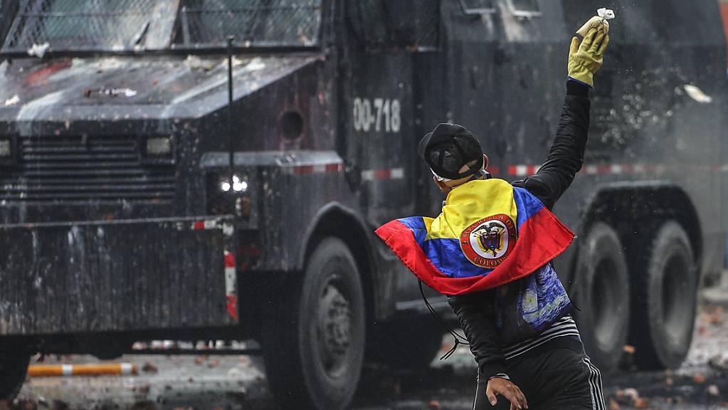 Ein wirft in einem Aussenbezirk von Bogotá einen Farbbeutel auf ein Polizeifahrzeug.