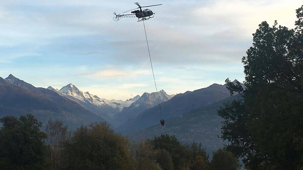 Ein Löschhelikopter holt im Umland von Savièse VS Wasser, um einen Waldbrand in der Nähe zu bekämpfen.