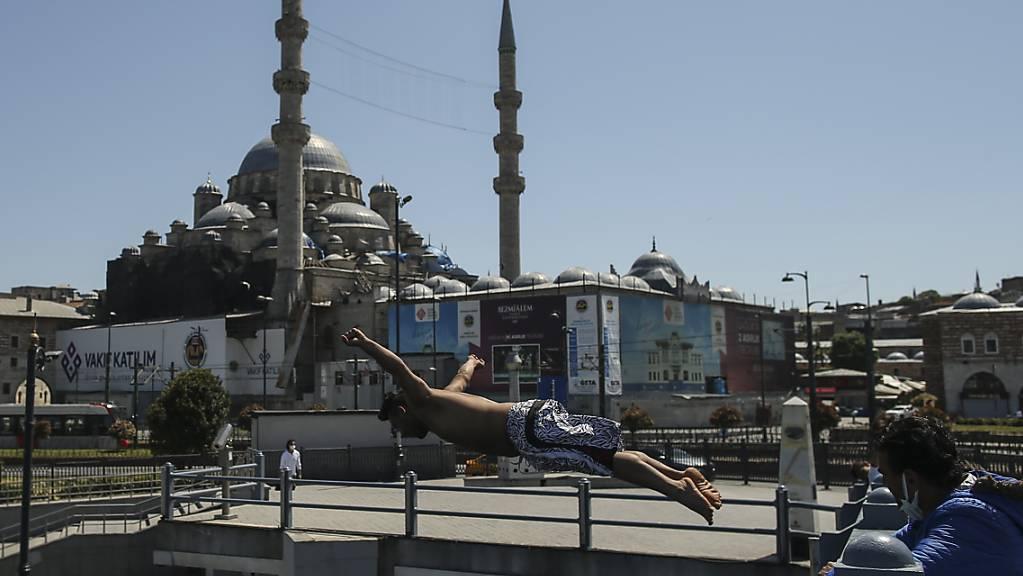 Vor dem Hintergrund der historischen Neuen Moschee springt ein Jugendlicher von der Galata Brücke in den Bosporus. Foto: Emrah Gurel/AP/dpa