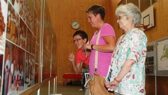 Interessiert werfen die Besucherinnen einen Blick auf die Fotos.