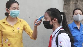 ARCHIV - Das Archivfoto aus dem Mai zeigt eine Fiebermessung bei einer Schülerin in Hanoi. Foto: Hau Dinh/AP/dpa