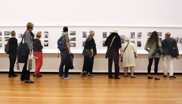 Besucher betrachten die zahlreichen Fotografien.