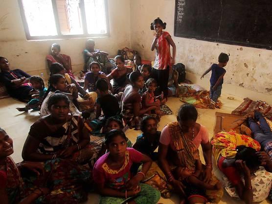 """Fischerleute und weitere Frauen und Kinder suchen in Konark im Osten Indiens in einem Haus Zuflucht vor dem Sturm """"Fani""""."""