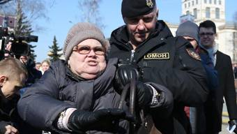 Polizist mit einer Demonstrantin in Minsk