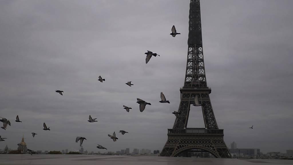 ARCHIV - Tauben fliegen am Eiffelturm vorbei. Wegen der Covid-19-Pandemie ist die Wiedereröffnung des Eiffelturms vorerst abgesagt worden. Foto: Thibault Camus/AP/dpa