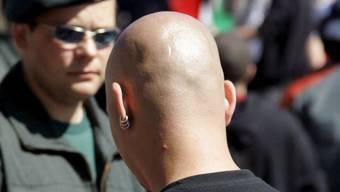 Ein Polizist beobachtet einen Neonazi bei einer Kundgebung in Deutschland (Symbolbild)