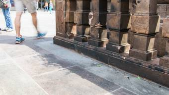 Mit schwarzem Russ bedeckte Steinplatten sind am Freitag auf dem Marienplatz in München zu sehen. In der Nacht auf Freitag hat sich an dieser Stelle ein Mann mit Benzin übergossen und selbst verbrannt.