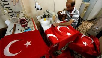 Politische Ungewissheit, wirtschaftliche Rückschläge: Wie geht es weiter mit der Türkei? Ein Mann näht Nationalflaggen in einem Geschäft in Istanbul. Murad Sezer/Reuters