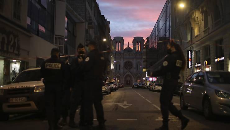 Polizisten gehen unter einem Absperrband vor der Kirche Notre Dame nach einem Messerangriff durch. Foto: Daniel Cole/AP/dpa