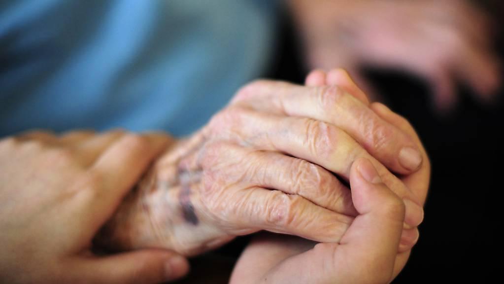 Eine Pflegekraft hält in einem Seniorenheim die Hand einer Bewohnerin.