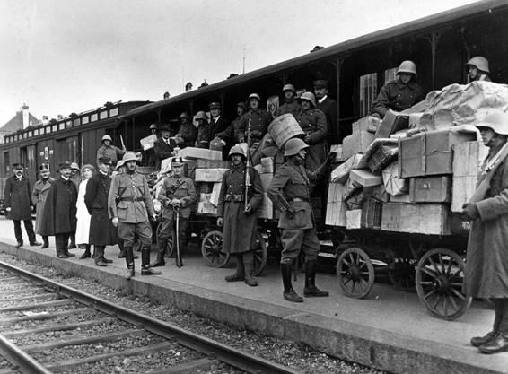 Im Bild: Eskortiert von Wachen werden Poststücke auf dem Bahnhof Bern von der Armee zum Eisenbahnpostwagen gebracht. Während des Generalstreiks von 1918 besorgen die aufgebotenen Truppen die Postbeförderung. (KEYSTONE/PHOTOPRESS-ARCHIV/Str)
