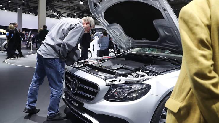 Der Autobauer Daimler musste die Erwartungen zurückschrauben: ein Mann begutachtet einen Mercedes (Archivbild).