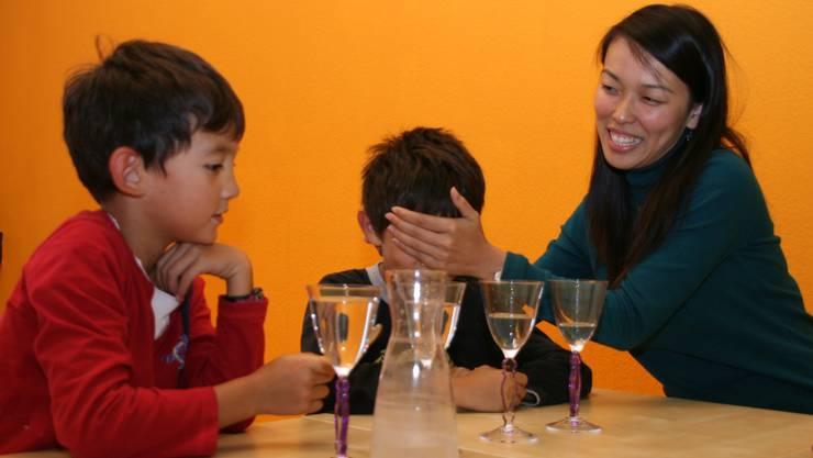 Christina Lim hält Christian die Augen zu. Er muss raten, an welches Glas Alexander mit dem Löffel schlägt.Gal