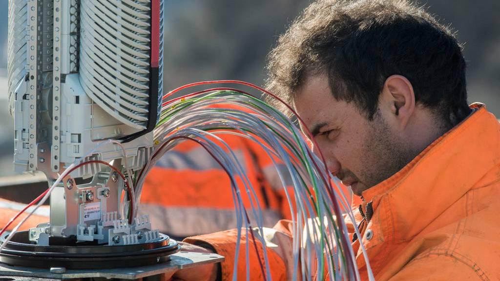Ein Arbeiter montiert das Glasfasernetz, das private Haushalte mit schnellem Internet bedient.