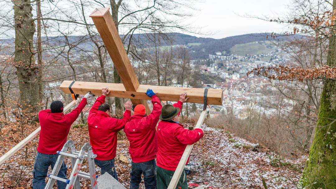 Die Mitarbeiter des Holzbaubetriebs Peterhans, Schibli & Co. stellen das Gipfelkreuz auf