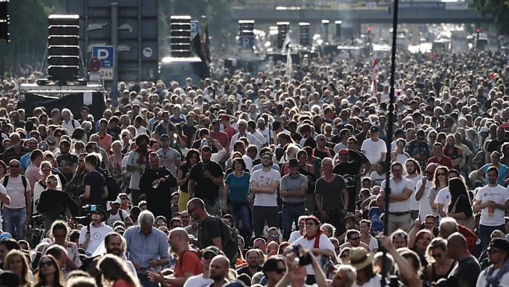 Teilnehmer einer Demonstration gegen die Corona-Maßnahmen stehen auf der Straße des 17. Juni. Foto: Michael Kappeler/dpa