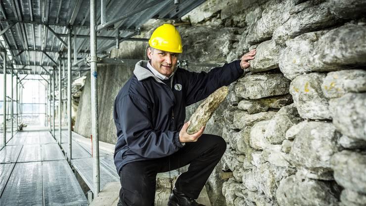 Projektleiter Rainer Kaufmann zeigt auf dem Gerüst einen losen Stein der Südwestmauer des Schlosses.
