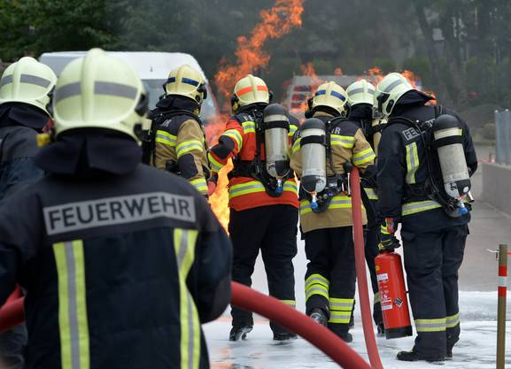 Mit Schaum und Atemschutz gegen das Feuer.